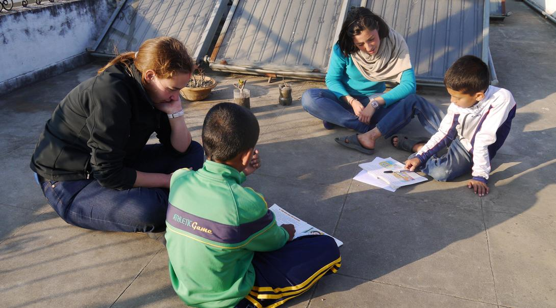 Projects Abroad volunteer help their students with their English reading in Nepal